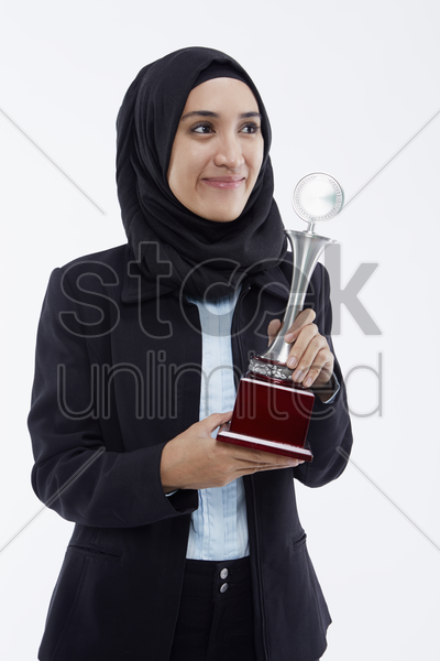 businesswoman with a winning trophy, smiling stock photo