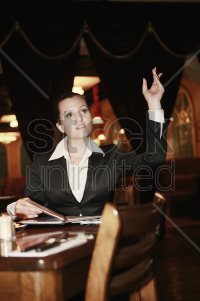 businesswoman with arms raised gesturing to waiter stock photo