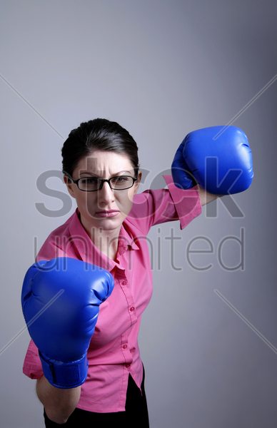 businesswoman with blue boxing gloves stock photo