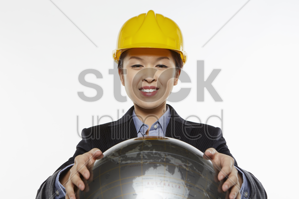 businesswoman with construction helmet holding a globe stock photo