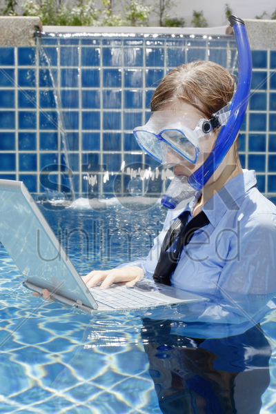 businesswoman with diving mask using laptop in swimming pool stock photo