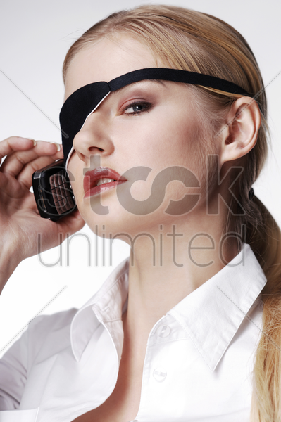 businesswoman with eye patch talking on the cell phone stock photo