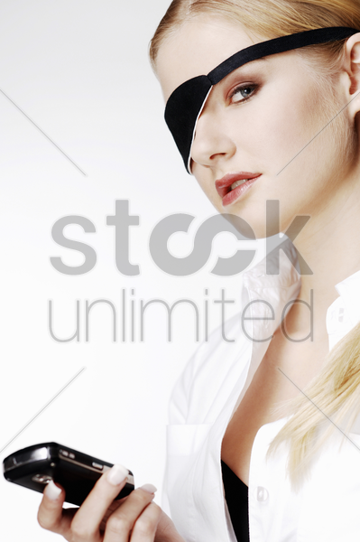businesswoman with eye patch text messaging on the cell phone stock photo