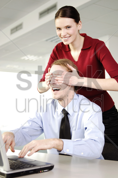 businesswoman with hands covering her colleague's eyes stock photo
