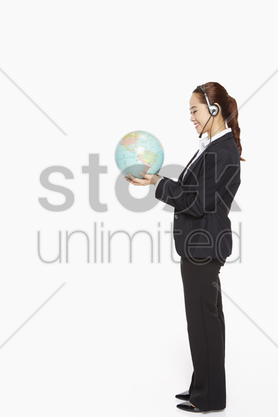 businesswoman with headset holding a globe stock photo