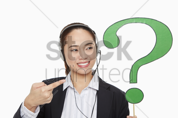 businesswoman with headset holding up a question mark symbol stock photo