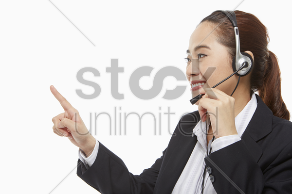 businesswoman with headset pointing to the right stock photo