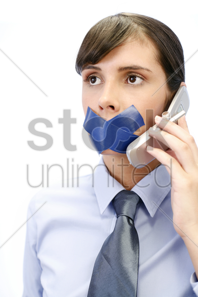 businesswoman with her lips sealed up trying to make a phone call stock photo