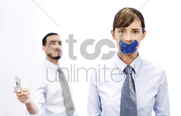 businesswoman with her lips sealed while her colleague is making phone call stock photo