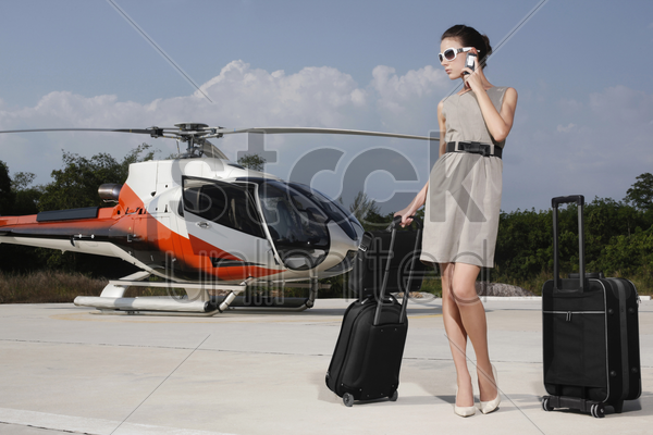 businesswoman with luggage and briefcase at helipad, talking on the phone stock photo