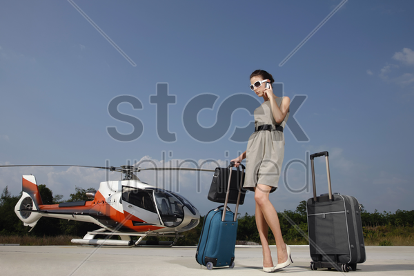 businesswoman with luggages and briefcase talking on the phone at helipad stock photo