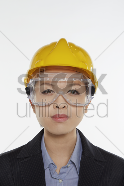 businesswoman with safety glasses and construction helmet smiling at the camera stock photo