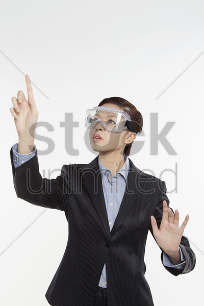 businesswoman with safety glasses showing hand gesture stock photo