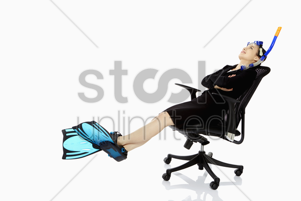 businesswoman with scuba diving gear resting on a chair stock photo