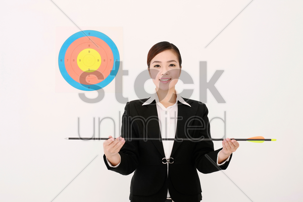 businesswoman with target next to her head, holding an arrow stock photo