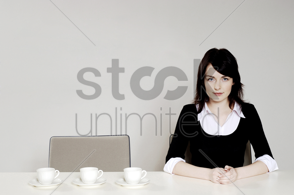 businesswoman with three coffee cups beside her stock photo