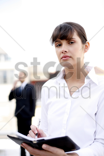 businesswoman writing down her schedule on the organizer stock photo