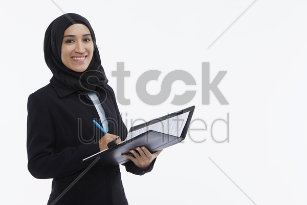 businesswoman writing down notes stock photo