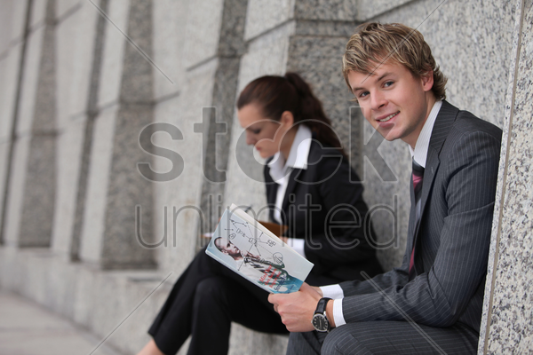 businesswoman writing in organizer, businessman reading a book stock photo