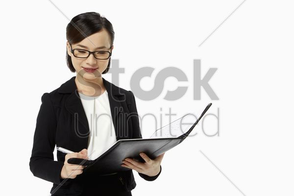 businesswoman writing notes in folder stock photo