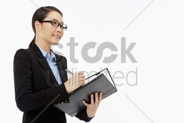 businesswoman writing notes in her folder stock photo