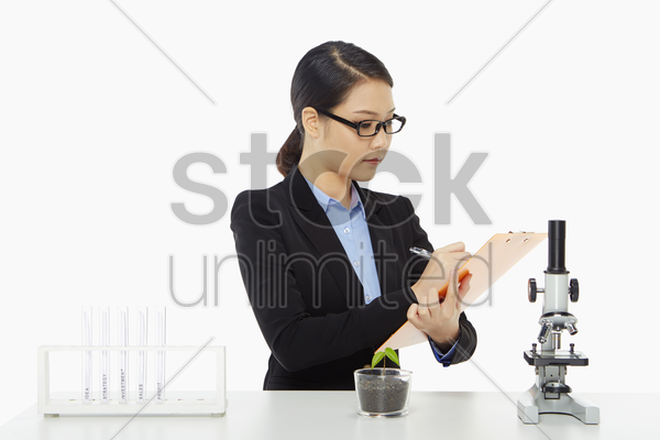 businesswoman writing notes on her clipboard stock photo