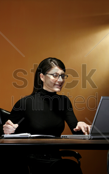 businesswoman writing while using laptop stock photo