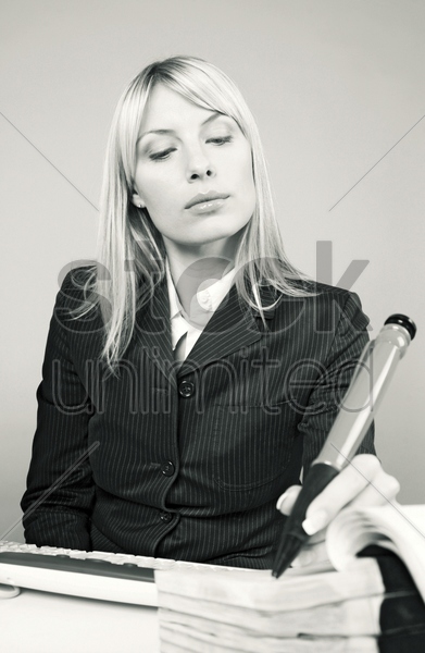 businesswoman writing with a big pen stock photo