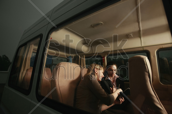 businesswomen having discussion and writing in organizer stock photo
