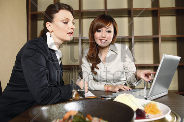 businesswomen having discussion over lunch stock photo