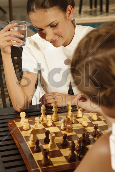 businesswomen playing chess by the poolside stock photo