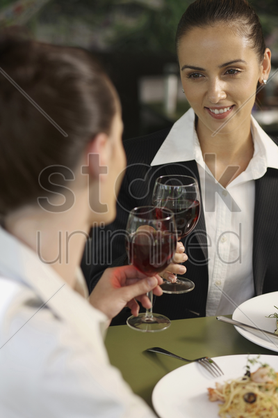 businesswomen raising their glasses stock photo