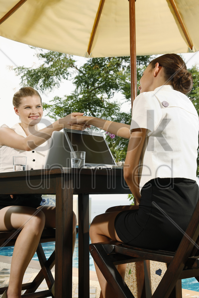 businesswomen shaking hands and smiling stock photo