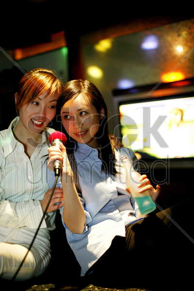 businesswomen singing karaoke after work stock photo