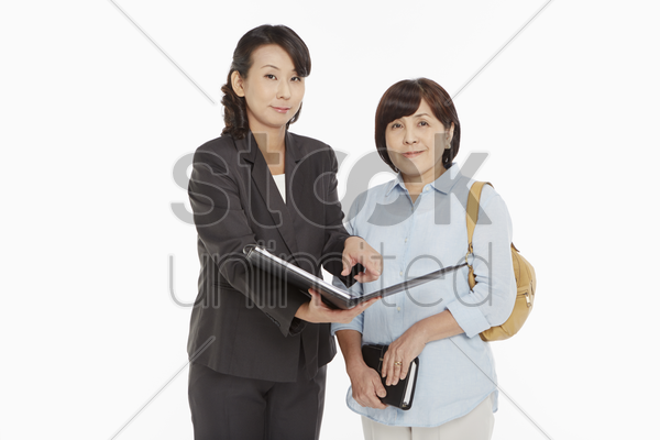 businesswomen taking a look at the folder stock photo