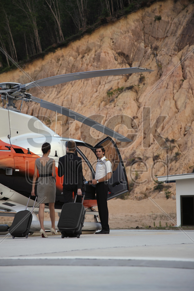 businesswomen walking towards helicopter, pilot waiting for them stock photo