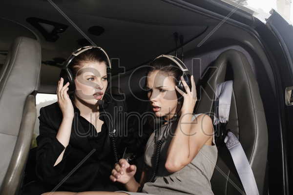businesswomen with headset in helicopter stock photo