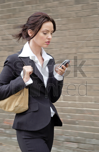 busy business woman text messaging while walking to work stock photo