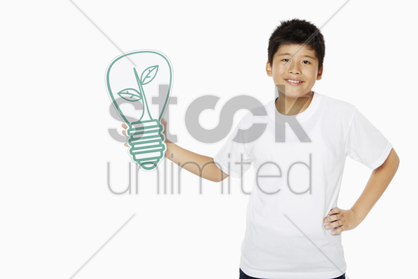 cheerful boy holding up a cut out light bulb stock photo