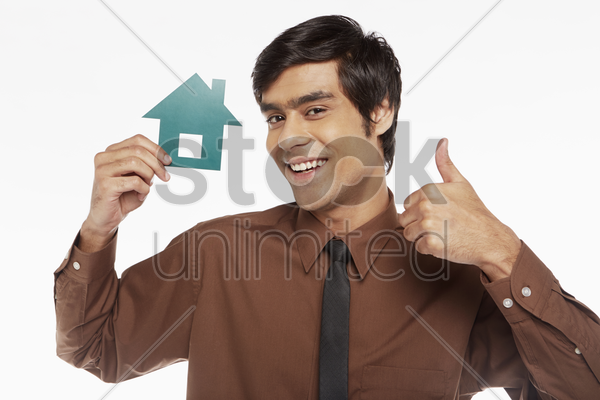 cheerful businessman holding up a cut out house stock photo