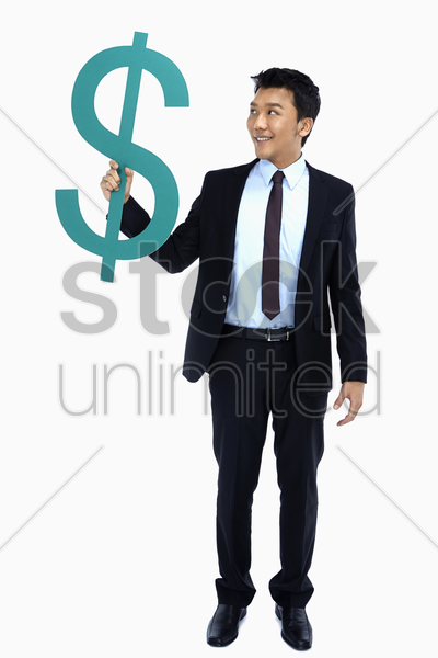 cheerful businessman holding up a dollar sign stock photo