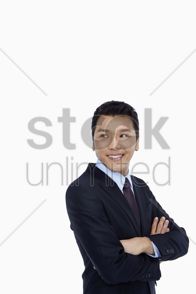 cheerful businessman standing with arms crossed stock photo