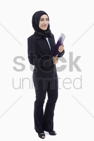 cheerful businesswoman carrying a folder stock photo
