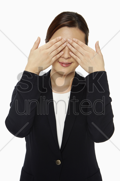 cheerful businesswoman covering her eyes stock photo