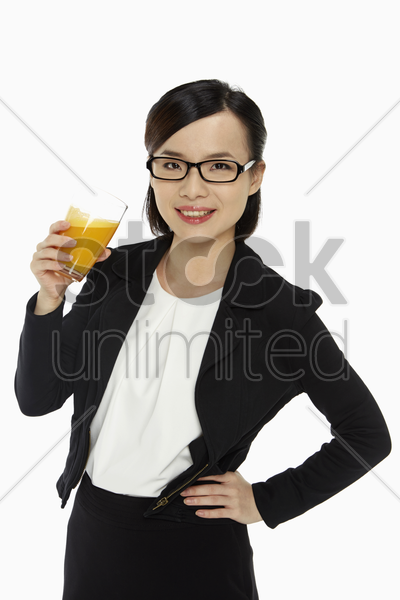 cheerful businesswoman holding a glass of orange juice stock photo