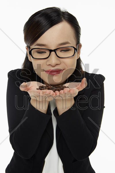cheerful businesswoman holding and smelling coffee beans stock photo