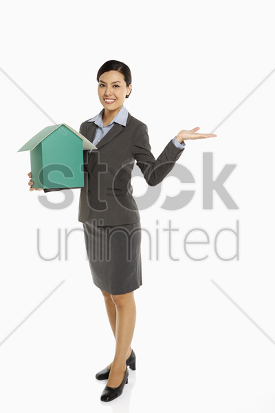cheerful businesswoman holding up a cardboard house stock photo