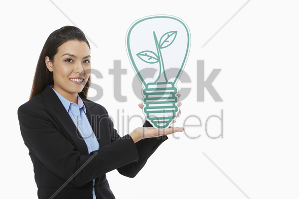 cheerful businesswoman holding up a cut out light bulb stock photo
