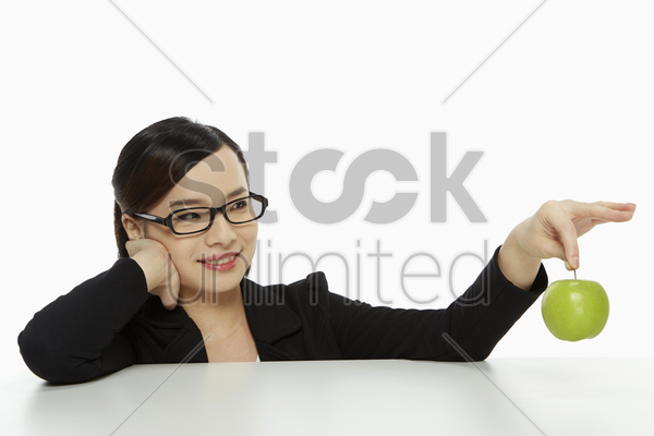 cheerful businesswoman holding up a green apple stock photo