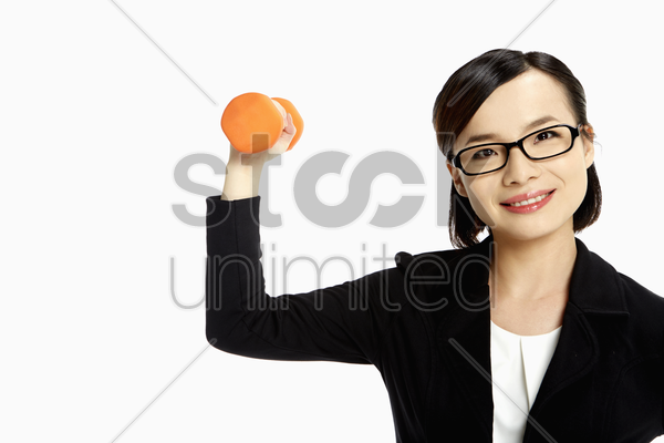 cheerful businesswoman lifting up dumbbell stock photo